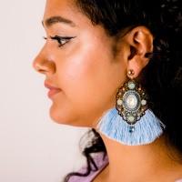 Goudkleurige oorstekers met statement hanger en lichtblauwe franjes